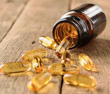 plusieurs gélules liquide d'huile de poissons posées sur une table en bois