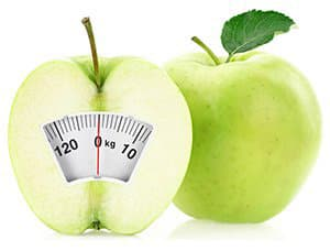 deux pommes vertes avec une balance sur un fond blanc