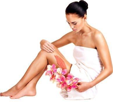 femme brune se caressant la peau de la jambes avec une fleur rose