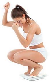 femme en petite tenue blanche se accroupi sur une balance