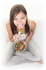 femme blanche souriante mangeant des fraises sur son canapé