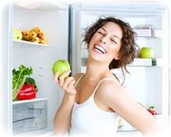 femme blanche avec une pomme verte dans la main devant son frigo