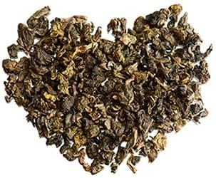tas de thé seché marron formant un coeur sur un fond blanc