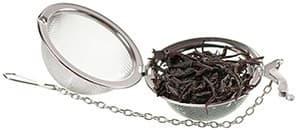 thé noir en vrac dans un égoutoir métallique sur un fond blanc
