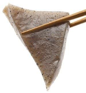 deux baguettes en bois tenant un morceau de pate de konjac