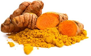 plusieurs fruit de curcuma découpés avec de la poudre oranges entreposés en vrac sur un fond blanc
