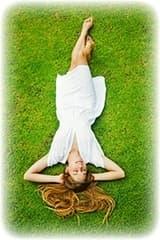 femme allongée dans l'herbe avec une rombe blanche