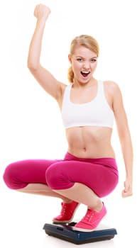 femme blanche levant le poing en l'air accroupi sur un pèse personne