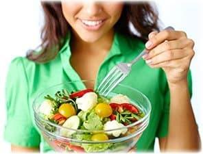 femme avec un chemiser vert mangeant une salade composée