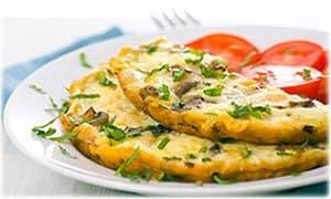 omelette coupée en deux avec des tomates et du persil