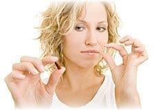 femme tenant deux gelules dans ses mains sur un fond blanc