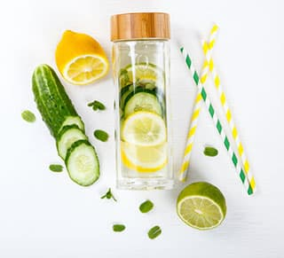 bouteille infuseur en verre avec fruits et legumes et paille en plastique