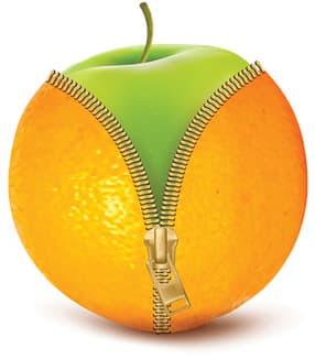 fausse orange ouverte sur une pomme verte sur un fond blanc