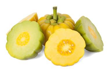 plusieurs fruits garcinia cambogia découpés en morceaux sur un fond blanc