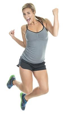 femme en tenue de sport sautant de joie sur fond blanc