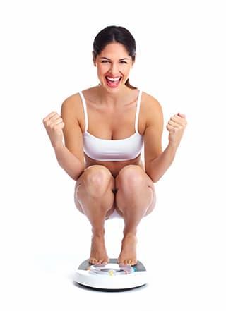 femme blanche souriant sur un pese personne et un fond blanc