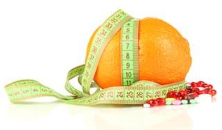 orange entourée d'un metre ruban et de gelules sur un fond blanc