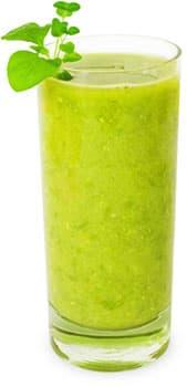 verre rempli d'une boisson verte healthy sur un fond blanc