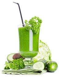grand verre rempli d'une boisson verte healthy sur un fond blanc