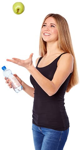 femme blanche lancant une pomme verte e l'air avec une bouteille d'eau
