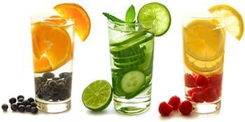 trois grand verres rempli de fruits avec de l'eau sur un fond blanc