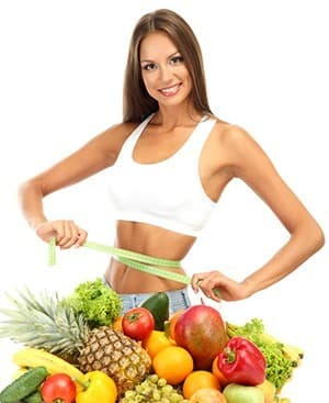 femme en tenue de sport et un tas de fruits multicolores