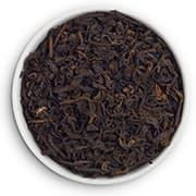 tas de thé marron dans une assiette blanche sur un fond blanc