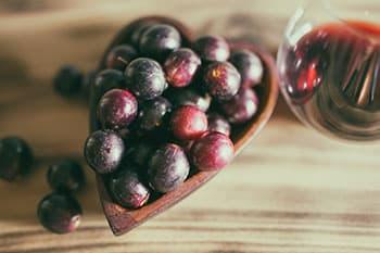 raisins rouges dans un recipient en bois sur une table en bois