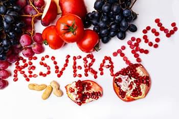 resveratrol ecrit avec des fruits multicolores sur un fodn blanc