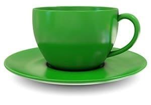 tasse verte posée sur une petite assiete sur un fond blanc