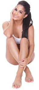 femme brune en petite tenue souriant sur un fond blanc