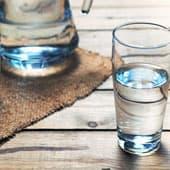verre en verre rempli d'eau sur une table en bois - weightworld