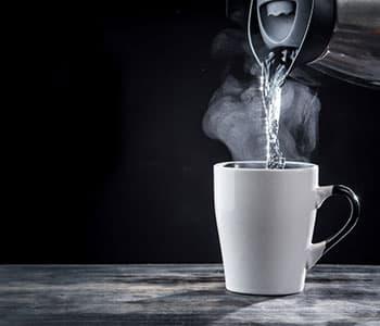 eau chaude versée d'une bouilloire dans une tasse à thé