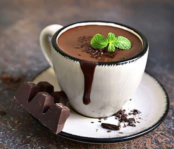 tasse de chocolat chaud sur une assiette avec un carré de chocolat