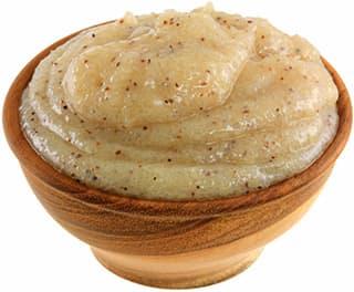 paquet de pate beige avec des morceaux rouge dans un bol en bois