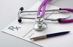 stetoscope posé sur une feuilel blanche à coté d'un stylo bleu