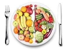 assiette de fruits et legumes accompagnée d'une fourchette et d'un couteau