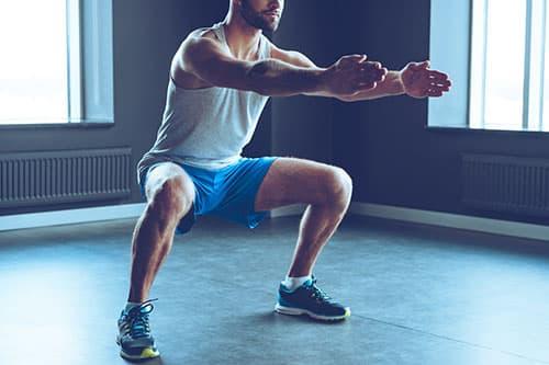 homme an train de faire des squats avec les bras tendus