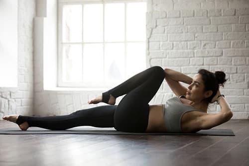 femme allongée sur un trapis en train de travailer ses abdominaux