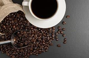 Tasse de café avec grains de café éparpillés autour