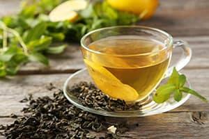 tasse de thé vert avec des feuilles de thé fraiches