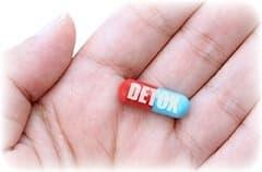 gelule detox rouge et bleu dans une main sur un fond blanc